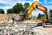 stock photo of crusher  - Hydraulic Concrete Crusher demolishing reinforced concrete structures - JPG