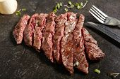 Thick Slices of Hot Grilled Whole Machete Steak or Skirt Steak on Black Stone Background. Fresh Juic poster