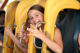 image of amusement park rides  - Cute girl ready to ride on a roller coaster - JPG