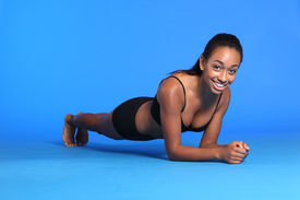 picture of knickers  - Stomach muscle building with the plank ab exercise lying on floor by a beautiful young athletic african american fitness woman wearing black sports bra and briefs underwear - JPG