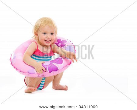 Baby Girl In Swimsuit Sitting With Inflatable Ring