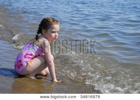 Young Girl Kneels In The Surf On A Beach.