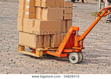 Courier Shipping Carboard Boxes On A Orange Trolly, On Stone Floor