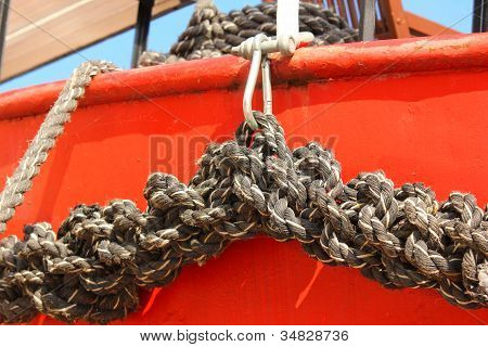 Close-up Of An Old Frayed Boat Rope, On A Red Boat