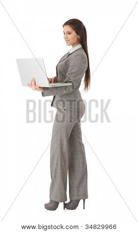 Attractive young businesswoman holding laptop in hands, working, smiling.