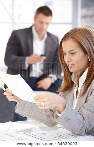 Young female working with papers in office, man texting in background.