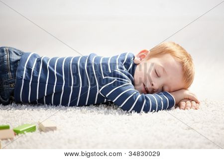 Cute 3 year old boy falling asleep on floor at home.