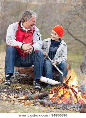 Grandfather and grandson around a campfire in the woods