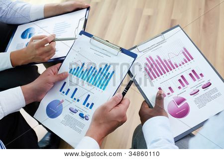 Image of business documents in human hands during discussion