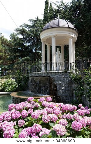 Nice arbour with waterfall in garden