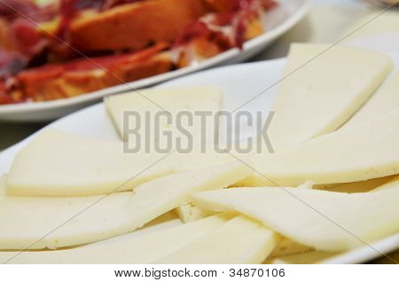 closeup of a plate with manchego cheese slices served as tapas