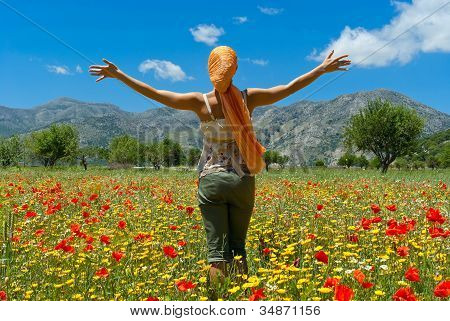Happy Young Woman Standing In Flower Colorful Field On Lasithi Plateau