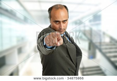 Businessman in a suit pointing, focus on the face
