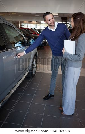 Man holding car handle in a dealership