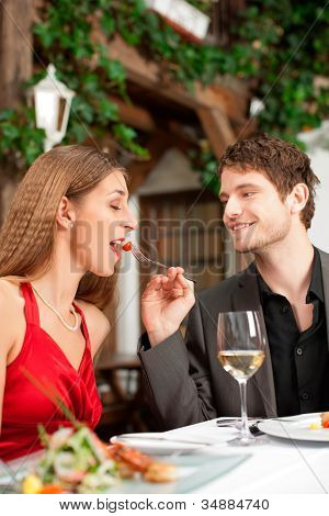 Couple on romantic date at a restaurant with food and wine
