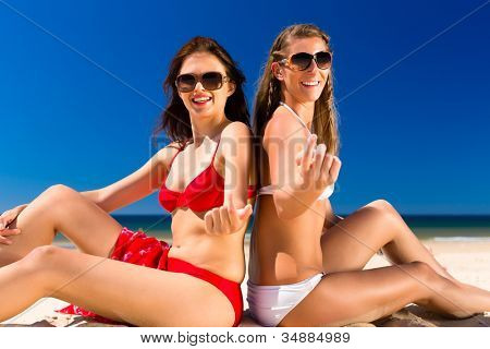 Two Girls enjoying freedom on the beach sitting in wind and sun at the sea