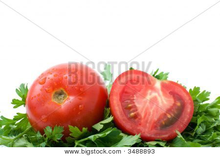 Whole And Half Of Tomato Over Some Parsley