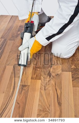 Appling Silicone Sealant In Spaces Of Old Wooden Floor
