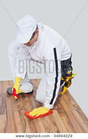 Arbeiter reinigt mit Handtuch und Spray Holzboden vor der Bodenbearbeitung