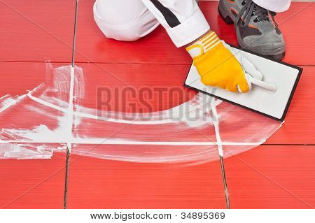 Worker With Rubber Trowel Applying Grout Tile