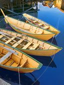picture of dory  - Group of traditional bright yellow painted wooden fishing dories roped together and moored at a dock in Lunenberg, Nova Scotia. Reflections of boathouses nearby. Vertical layout.