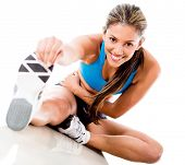 stock photo of gym workout  - Fit woman stretching her leg to warm up  - JPG