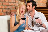 Attractive young couple drinking red wine in restaurant or bar, it might be the first date