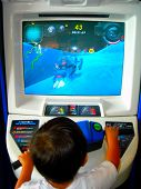pic of arcade  - boy playing video game at indoor video arcade - JPG