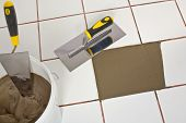stock photo of mortar-joint  - Repaired Old White Tiles Floor With Trowel And Tile Adhesive - JPG