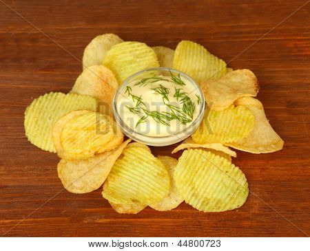 Potato chips and sauce, on wooden background