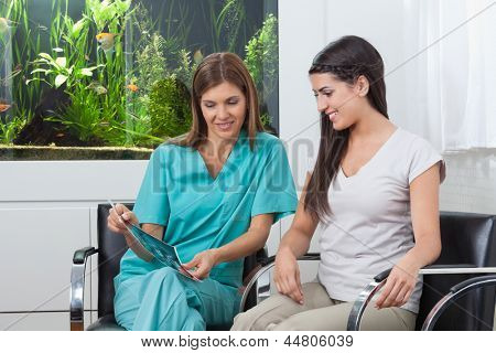 Female dentist showing X-ray report to young woman in clinic