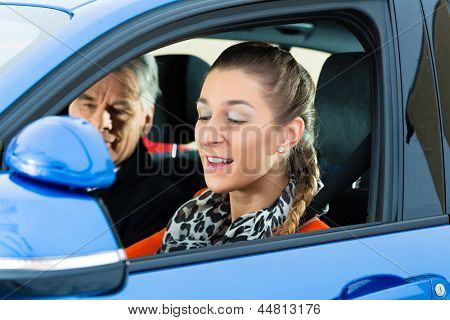 Driving School - Young woman steer a car, maybe she has a driving test perhaps she exercises the parking