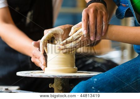 Female Potter creating a bowl on a Potters wheel, the master potter helping her
