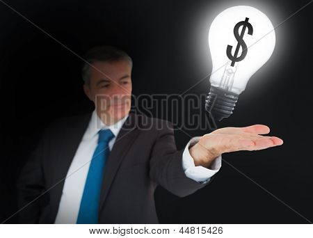 Businessman showing light bulb with dollar symbol