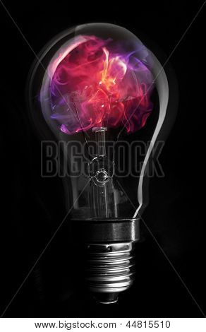 Pink flame inside light bulb on black background