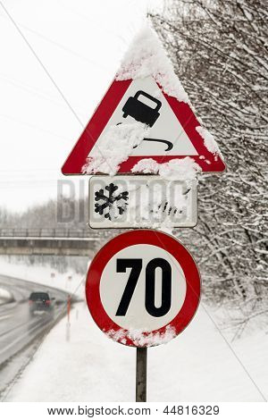 traffic signs and snow, symbol photo for winter weather, accident risk and speed limit