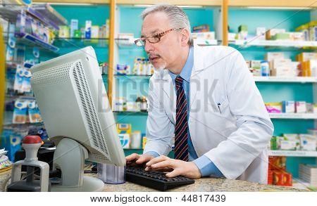 Retrato de um farmacêutico usando um computador desktop