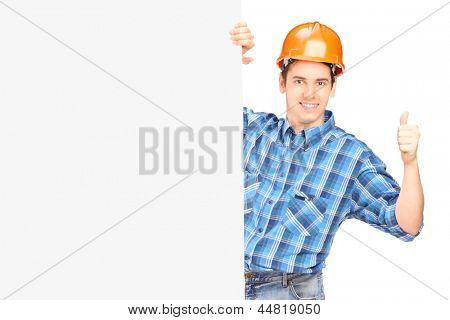 A male worker with helmet posing behind a blank panel and giving thumb up isolated on white background