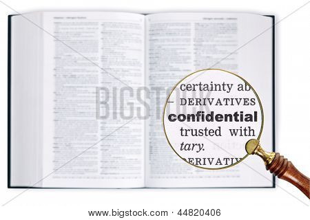 A magnifying glass held over a dictionary looking at the word Confidential enlarged