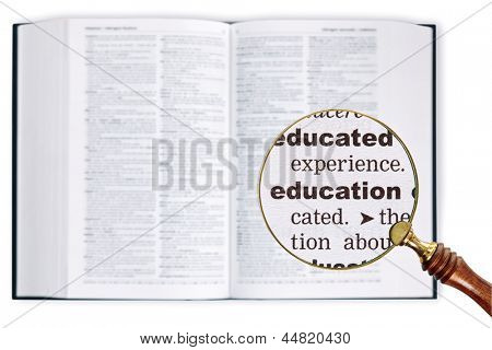 A magnifying glass held over a dictionary looking at the word Education enlarged
