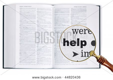 A magnifying glass held over a dictionary looking at the word Help enlarged