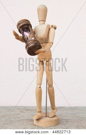 Wood Mannequin And Hourglass To Represent Time Caring