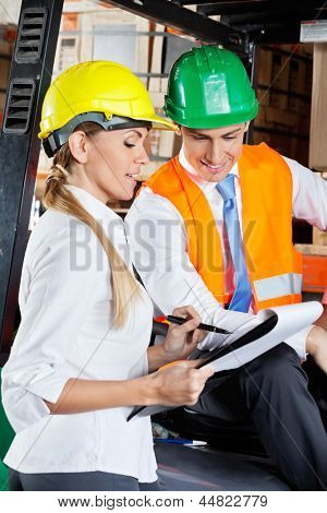 Female supervisor communicating with colleague sitting in forklift at warehouse