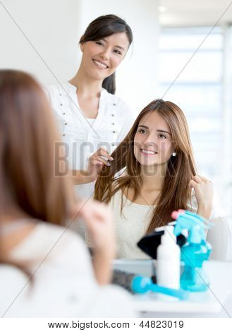 Woman at the hairdresser for a haircut getting advice from stylist