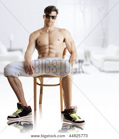 Portrait of a hot muscular male model shirtless in sunglasses in modern bright studio interior