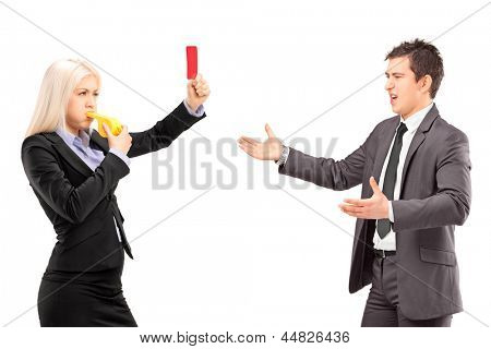 Woman in business suit showing a red card and blowing a whistle to a man in a business suit, isolated on white background