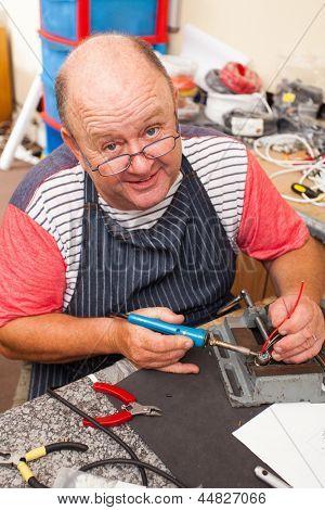 happy senior technician working with soldering iron in workshop