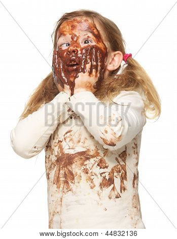 Portrait Of A Funny Little Girl With Dirty Face Covered In Chocolate