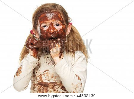 Portrait Of A Little Girl Eating Chocolate Bar And Face Covered In Chocolate