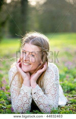 Young Woman Smiling Lying On Grass And Flowers